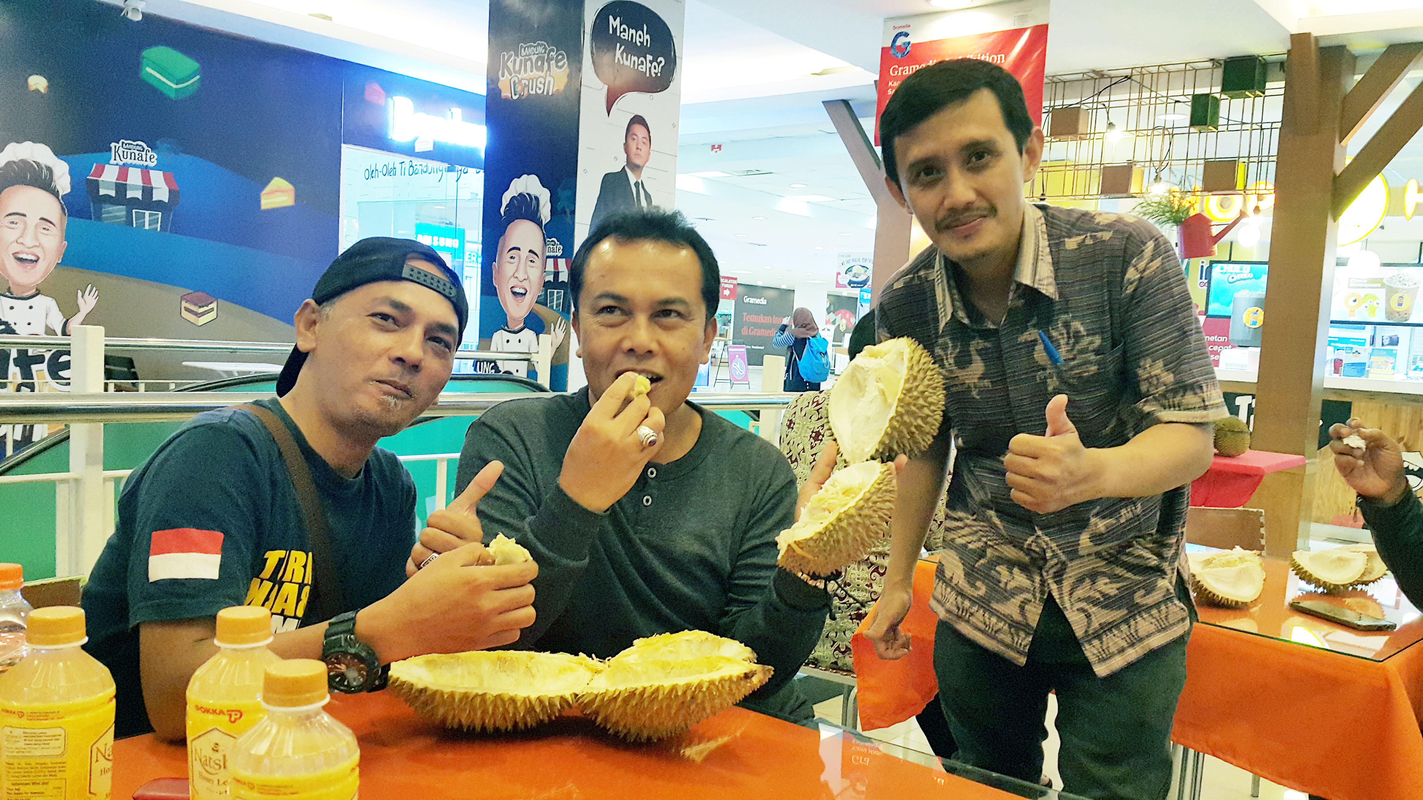 Para pengunjung Miko Mall tampak sangat menikmati makan buah durian dalam acara festival makan durian sepuasnya yang digelar pihak panitia.